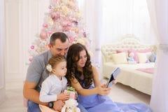 现代家庭与Skype的亲戚谈话在宽敞卧室 免版税库存照片
