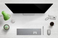 现代家庭书桌工作场所 与键盘、老鼠、笔、拨号盘、灯、植物、咖啡和数字照相机的计算机显示器 免版税库存照片