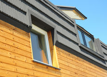 现代屋顶建筑和大厦新房有天窗、顶楼、屋顶窗和屋顶的Windows 免版税库存照片