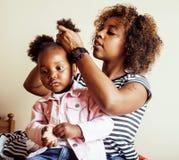 现代年轻愉快的非裔美国人的家庭:照顾在家梳女儿头发,生活方式人概念 免版税图库摄影