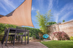 现代房子大阳台在与树荫风帆的夏天 免版税库存照片