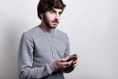 现代技术和通信概念 有胡子的英俊的行家男孩在举行他智能手机听的白色耳机 库存图片