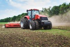 现代技术红色拖拉机在春天的犁一个绿色农业领域在农场 收割机播种麦子 免版税库存图片