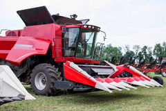 现代技术红色拖拉机在春天的犁一个绿色农业领域在农场 收割机播种麦子 图库摄影