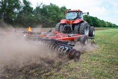 现代技术红色拖拉机在春天的犁一个绿色农业领域在农场 收割机播种麦子 库存图片