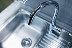现代轻拍龙头和水槽在新的厨房 免版税库存图片