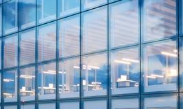 现代摩天大楼内部特写镜头照片  在晚上时间的办公室地板 全景窗口门面背景 库存照片