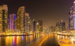 现代摩天大楼在有繁忙的运河的在晚上,迪拜,阿联酋豪华迪拜小游艇船坞 库存照片