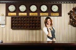 现代旅馆逆书桌的接待员  免版税库存照片