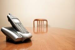 现代无线电话坐一张空的桌 免版税库存照片