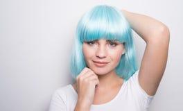 现代未来派样式的厚颜无耻的女孩与摆在白色的蓝色假发 库存照片