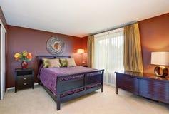 现代样式的主卧室与棕色墙壁和地毯地板 免版税库存照片