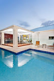 现代游泳池在与豪华豪宅或旅馆bes的晚上 图库摄影