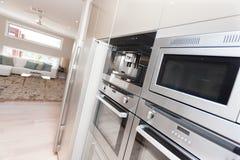 现代烤箱和一个冰箱特写镜头在豪华kitc 免版税图库摄影