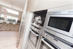 现代烤箱和一个冰箱特写镜头在豪华kitc 免版税库存照片