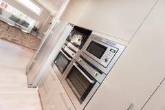 现代烤箱和冰箱固定在有餐具室cupbo的墙壁 免版税库存照片