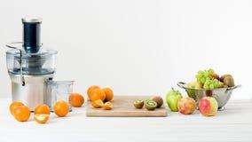 现代电榨汁器和各种各样的果子在厨台,健康生活方式 库存图片