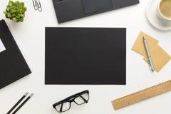 现代白色办公桌顶视图有黑纸的在中心 免版税库存图片