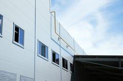 现代白色大厦的门面与黄色天然气管子在正面图和蓝天的在背景 库存图片