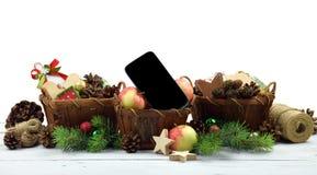 现代的生活 在一个土气样式和智能手机的圣诞节闪亮金属片 库存图片