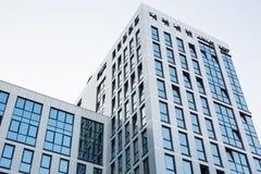 现代的结构 有反射明亮的蓝天的小半开窗口的透明墙壁 抽象背景玻璃 免版税库存照片