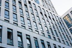 现代的结构 有反射明亮的蓝天的小半开窗口的透明墙壁 抽象背景玻璃 库存图片
