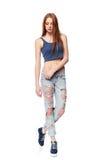 现代红发女性佩带的困厄的牛仔裤 免版税库存照片
