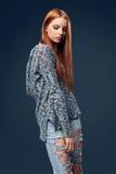 现代红发女性佩带的困厄的牛仔裤 库存照片