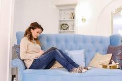 现代美丽的妇女坐互联网和纸卷在片剂ne 免版税库存照片