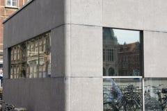 现代老 古老的大厦和自行车的反射在一个现代大厦的窗口里 免版税库存图片