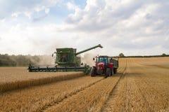 现代联合收割机切口播种玉米工作金黄领域的麦子大麦 免版税库存图片