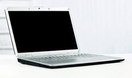 现代膝上型计算机在有黑屏的一个明亮的办公室文本的 免版税库存照片