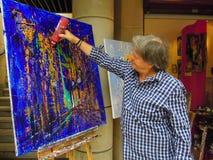 现代艺术家滴下从塑料瓶的油漆在他的帆布上 库存图片