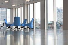 现代蓝色椅子在窗口的新的空的办公室 库存图片