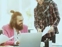 现代设计师和他的队在一个创造性的演播室开发衣裳新的模型  免版税库存图片