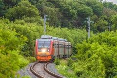 现代通勤者乘客红色火车沿一条单线的铁路移动 免版税库存图片