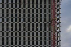 现代铁具体墙壁的片段纹理有窗口的没有玻璃 新的多层的大厦门面  免版税库存照片