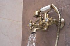 现代水龙头在卫生间里 流动的水 库存照片