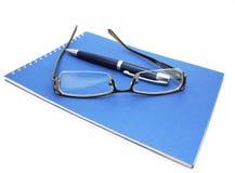 玻璃、笔和笔记本 免版税库存图片
