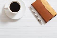 玻璃、笔记本、笔和咖啡在白色木backgro的 库存图片