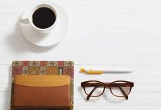 玻璃、笔记本、笔和咖啡 库存照片