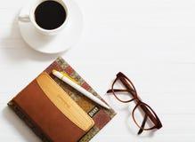 玻璃、笔记本、笔和咖啡 库存图片