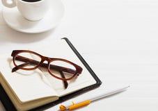 玻璃、笔记本、笔和咖啡 免版税库存照片