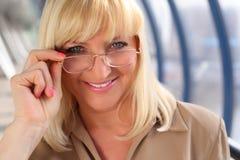 玻璃中年微笑的妇女 免版税库存图片