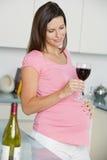 玻璃厨房怀孕的红葡萄酒妇女 库存图片