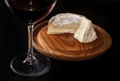 玻璃和一个瓶红葡萄酒,在一块木板材的咸味干乳酪乳酪, 库存照片