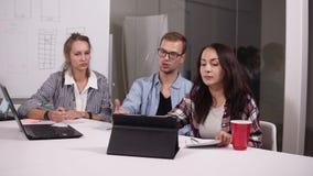玻璃和两名妇女的年轻人偶然开会的在与膝上型计算机和片剂的办公室桌上对此在创造性 股票视频