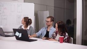 玻璃和两名妇女的年轻人偶然开会的在办公室桌上在有膝上型计算机的创造性的工作场所对此 人 影视素材