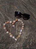 玻璃和壳在海滩 库存照片