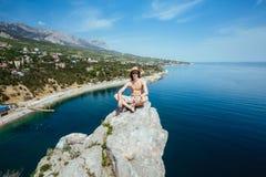 玻璃和帽子的年轻愉快的微笑的人坐岩石的边缘 免版税图库摄影